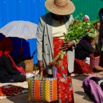 Villager at local market with handwoven basket and flowers