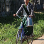 School child on bicycle with handwoven basket and lunchbox tiffin tin