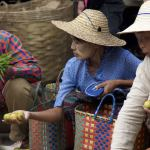 Myanmar village market with villagers shopping for local produce with baskets